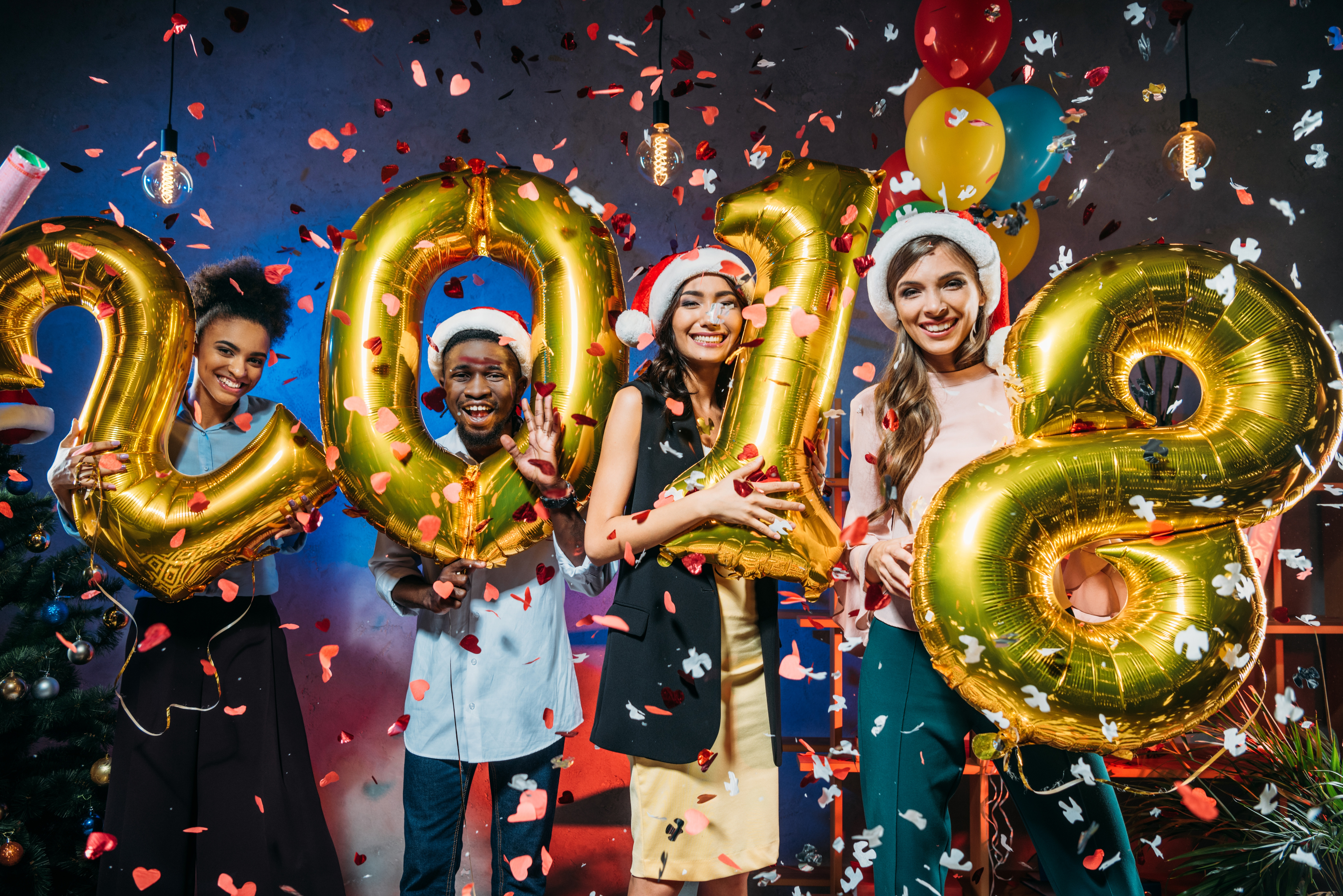 four people holding up numbers 2018 with confetti