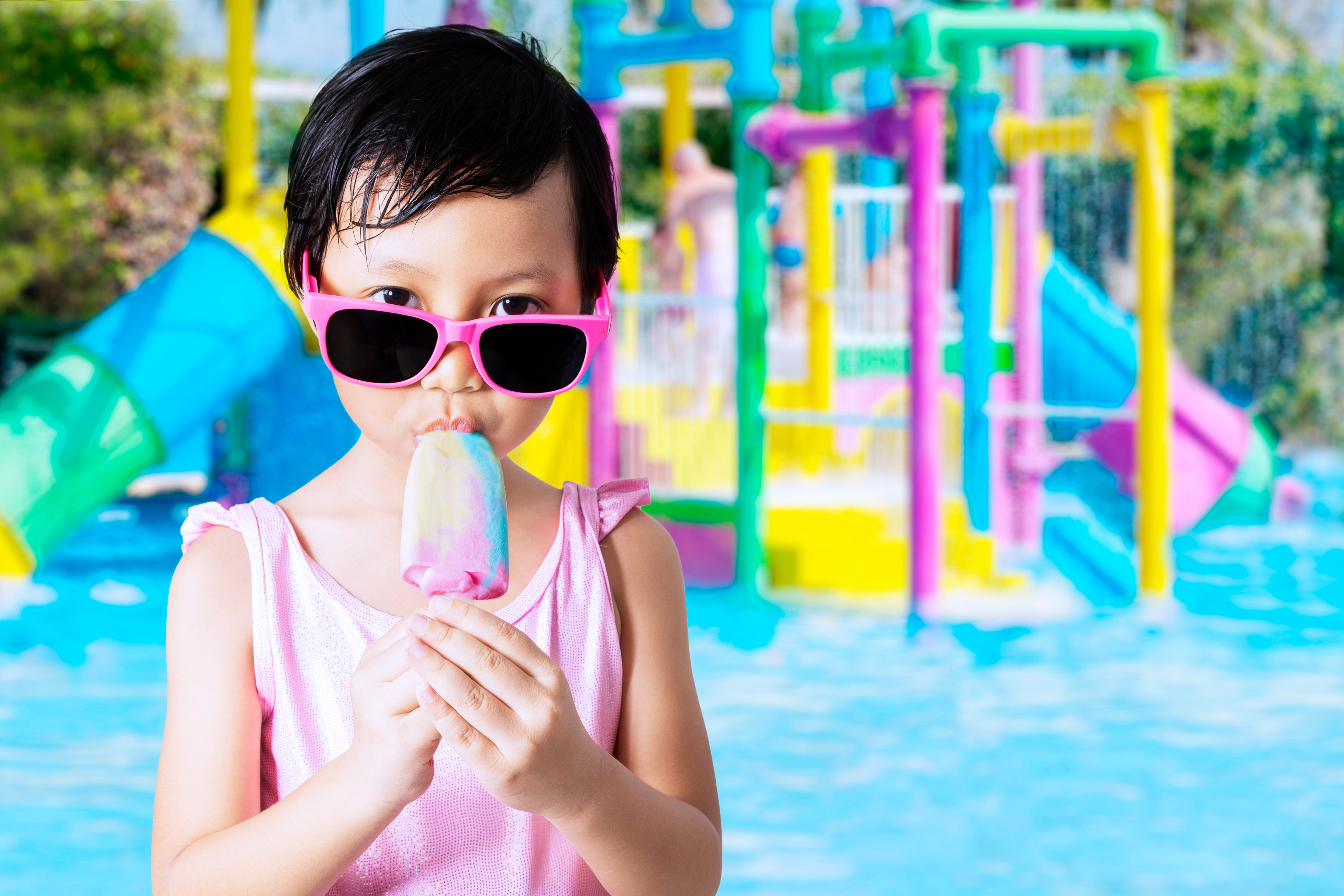 little girl in pink bathing suit eating popsicle at water park