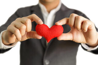 Man's hands holding small red stuffed heart