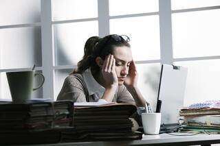 woman hands on head frustrated at desk
