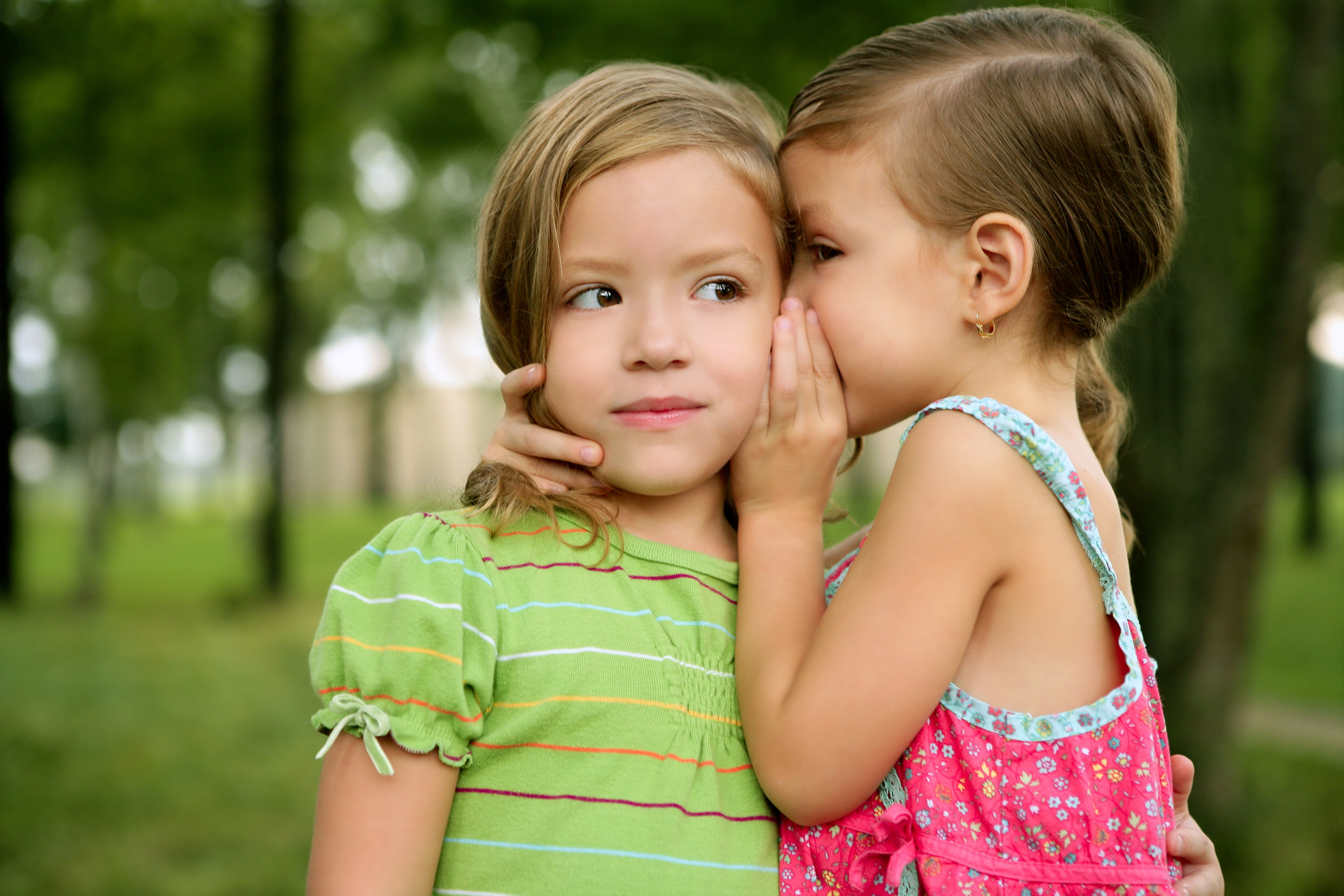 two little girls one whispering to the other