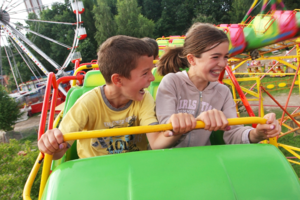 young boy and girl on green roller coaster